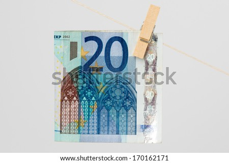 Close-up of Euro bill hanging on a light thread. - stock photo
