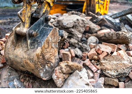 close-up of excavator bucket loading rocks, stones, earth and concrete bricks from demolition site - stock photo
