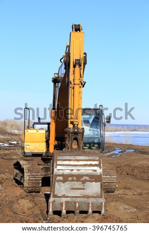 close-up of excavator on the river bank in early spring - stock photo