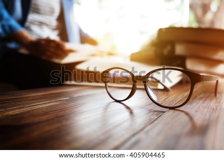 Close up of eye glasses on wood desk and text book in library. Education concept. - stock photo