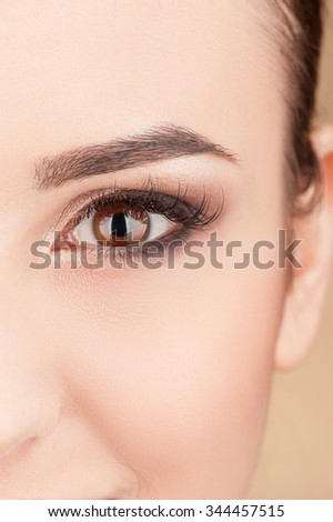Close up of eye of cute young woman looking forward happily. She is receiving make-up treatment - stock photo