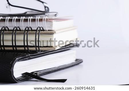 Close up of Eyeglass on books stack horizontal side on white background