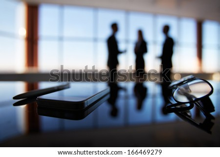 Close-up of eyeglasses, cellular phone and pen at workplace on background of office workers interacting - stock photo