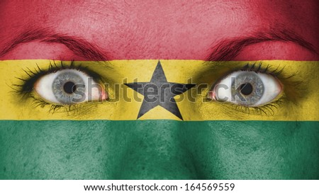 Close up of eyes. Painted face with flag of Ghana - stock photo