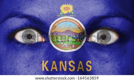 Close up of eyes. Painted face with flag of Kansas - stock photo