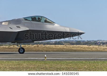 Close-up of F-22 Raptor fighter bomber landing on runway. - stock photo