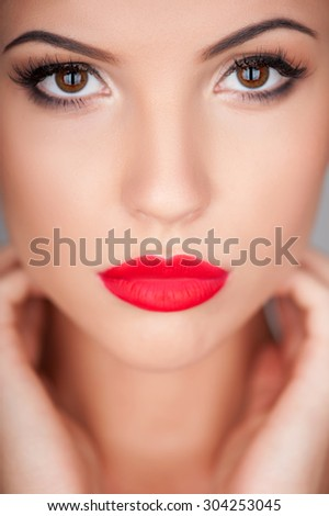 Close up of face of beautiful girl touching her body with passion. She is looking forward with temptation - stock photo