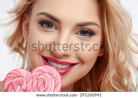 Close up of face of cheerful woman touching candy to her lips. She is smiling and looking at the camera with desire - stock photo