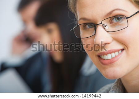 Close-up of face of clever smiling businesswoman with glasses - stock photo