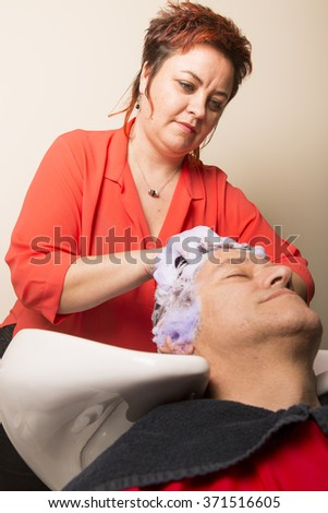 Close up of face of man is getting a hairwash by a hairdresser, with relaxation. The beautician is making foam from shampoo