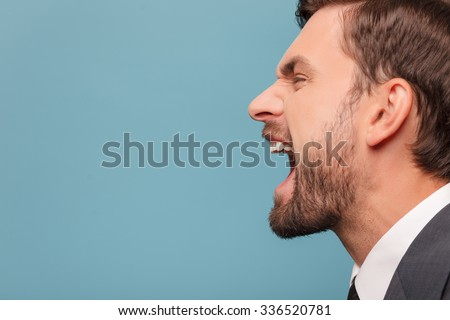 Close up of face of man shouting with anger. He is standing in profile. Isolated on blue background. Copy space in left side - stock photo