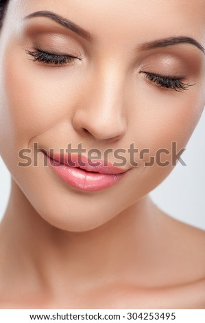 Close up of face of pretty woman. She closed her eyes with pleasure. The lady is gently smiling. She has beautiful complexion