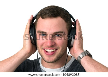 Close up of face of young man in grey t-shirt listening to music with earphones