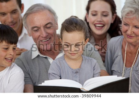 Close-up of family looking at a photograph album at home - stock photo