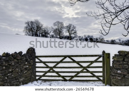 Close up of farm gate in snow covered countryside, winter scene. - stock photo