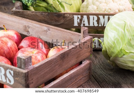 Close up of farmers crate with ripe apples and cabbage on a wooden background. - stock photo