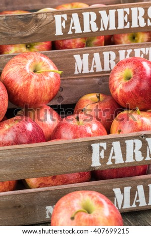 Close up of farmers crates with ripe apples on a wooden background. - stock photo