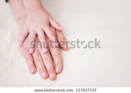 Close up of father and daughter hands on sand - stock photo