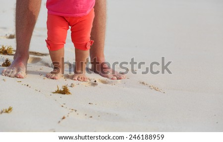 Close up of father and little daughter feet on a tropical beach - stock photo