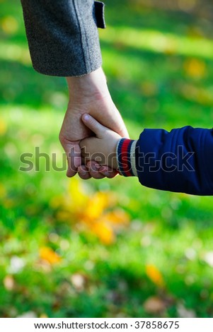 Close up of father and son hands outdoors at autumn day - stock photo