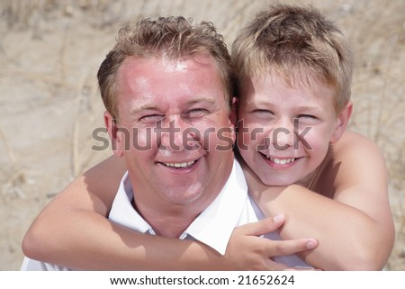 close-up of father and son having fun on the beach - stock photo