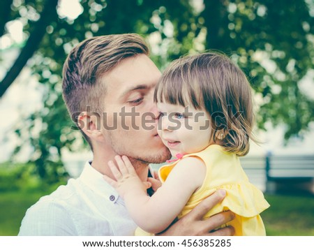 Close up of father holding his crying daughter. Dad kissing his little daughter - stock photo