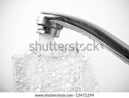 Close-up of faucet pouring water into glass. Black and white. Shallow DOF.