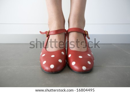 close-up of feet in red shoes with white dots - stock photo
