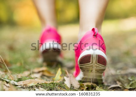 Close up of feet of a runner running in autumn leaves training exercise - stock photo