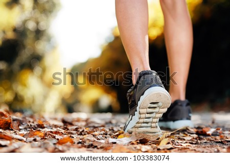 close up of feet of a runner running in autumn leaves training for marathon and fitness healthty lifestyle