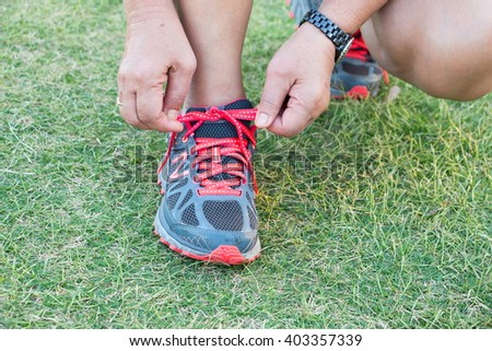 Close up of feet of a runner tying shoe laces in green grass  training exercise