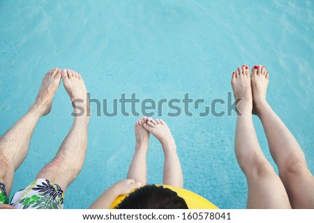 Close-up of feet of family in the pool - stock photo