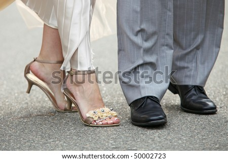 Close-up of feet of newly-married couple, outdoor shot - stock photo