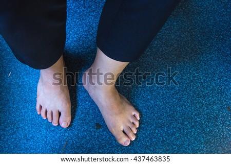 Close up of feet on blue carpet - stock photo