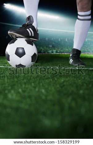 Close up of feet on top of soccer ball - stock photo