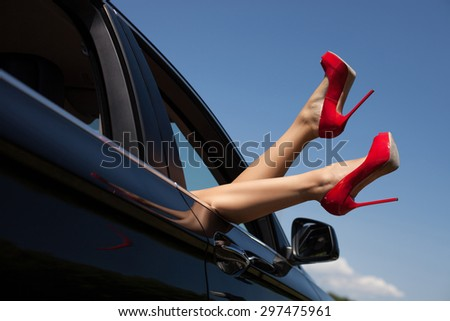 Close-up of feet with red shoes on high heels of attractive girl. She is putting her legs through the window of modern transport - stock photo