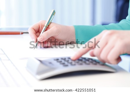 Close-up of female accountant making calculations while sitting at desk in office.  - stock photo