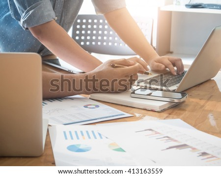 Close-up of female and male hands pointing at turnover graph while discussing it in office. group support concept. - stock photo