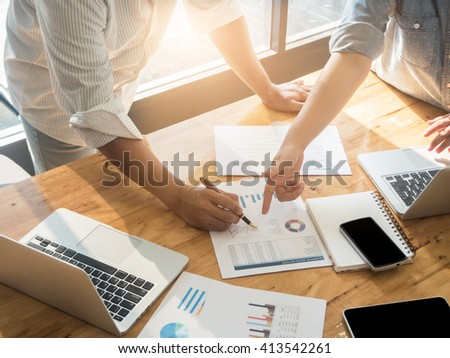 Close-up of female and male hands pointing at turnover graph while discussing it on wooden desk in office. group concept. - stock photo