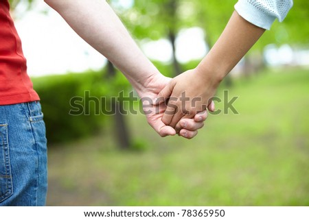 Close-up of female and male holding by hands in park