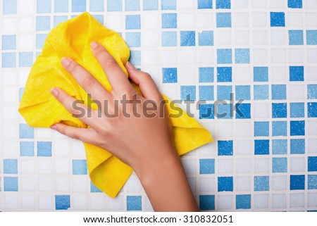 Close up of female arm of cleaner washing tile on wall in bathroom with yellow washcloth - stock photo