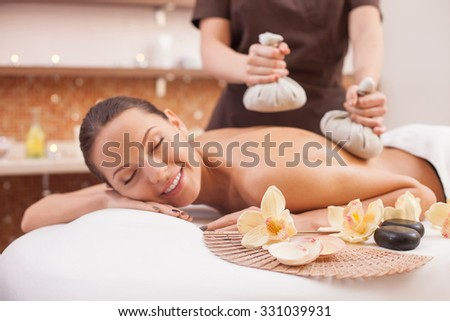 Close up of female arms of masseuse massaging client with textile massage spa equipment. The woman is lying and relaxing. She closed her eyes with joy and smiling - stock photo