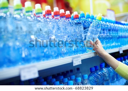 Close-up of female choosing good mineral water in a shop - stock photo