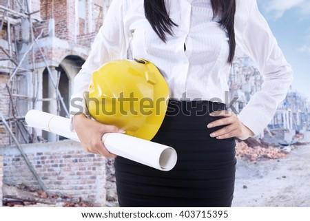 Close up of female contractor standing at the construction site while holding a blueprint and helmet - stock photo