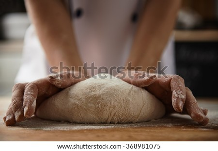 Close-up of female cook hands kneading dough for pizza or pasta in the kitchen. Healthy food preparation. - stock photo