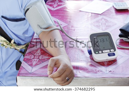 Close-up Of Female Doctor Checking Blood Pressure Of Male Patient - stock photo