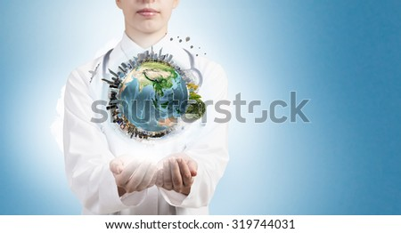 Close up of female doctor holding Earth planet in hands. Elements of this image are furnished by NASA - stock photo