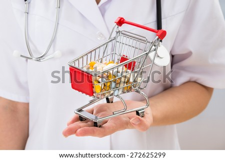 Close-up Of Female Doctor Holding Shopping Cart With Full Of Pills - stock photo