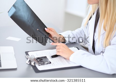 Close up of female doctor holding x-ray or roentgen image, sitting at the table - stock photo