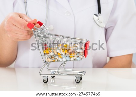 Close-up Of Female Doctor With Shopping Cart Full Of Pills At Desk - stock photo